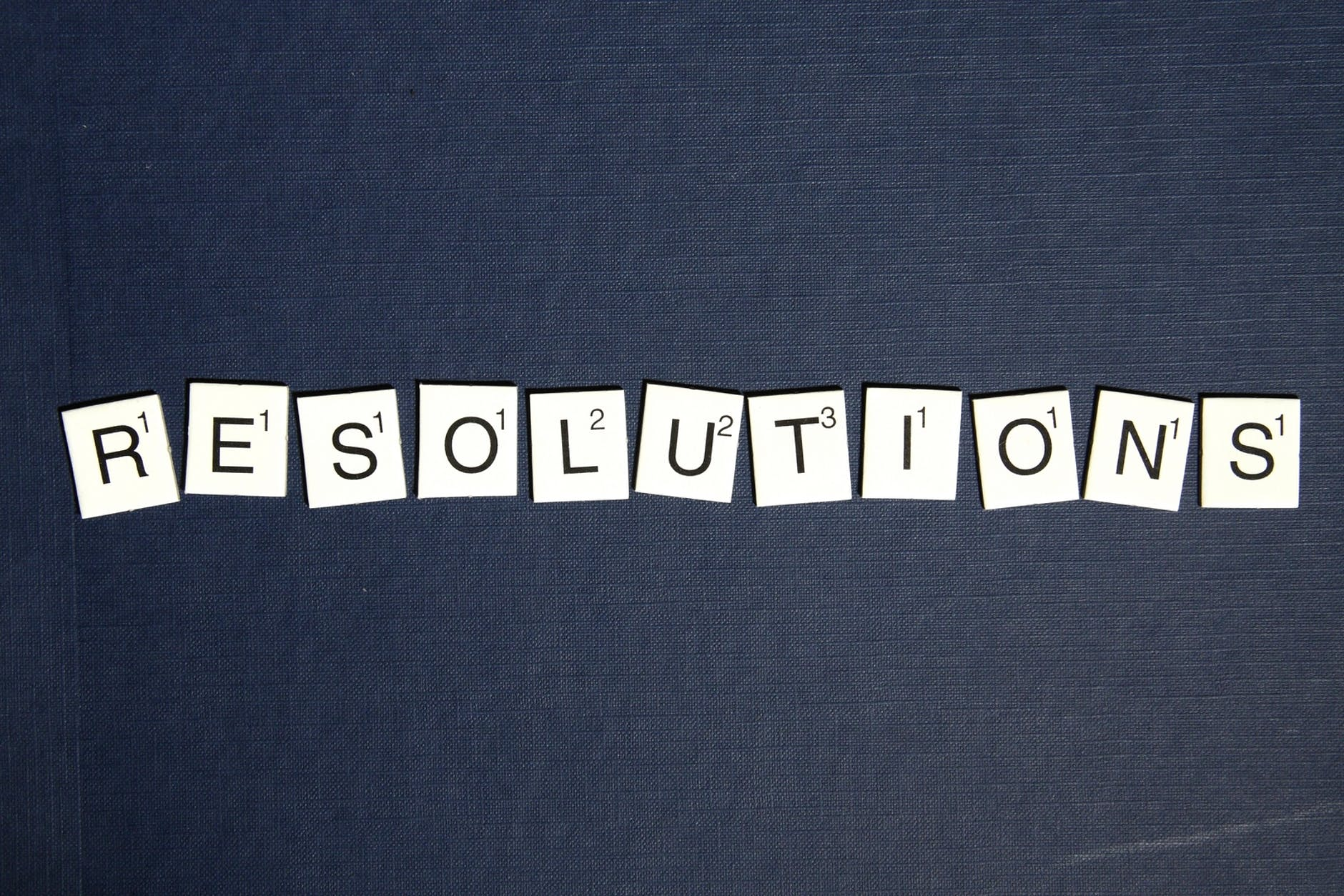 New Year's resolutions spelled out with Scrabble tiles.