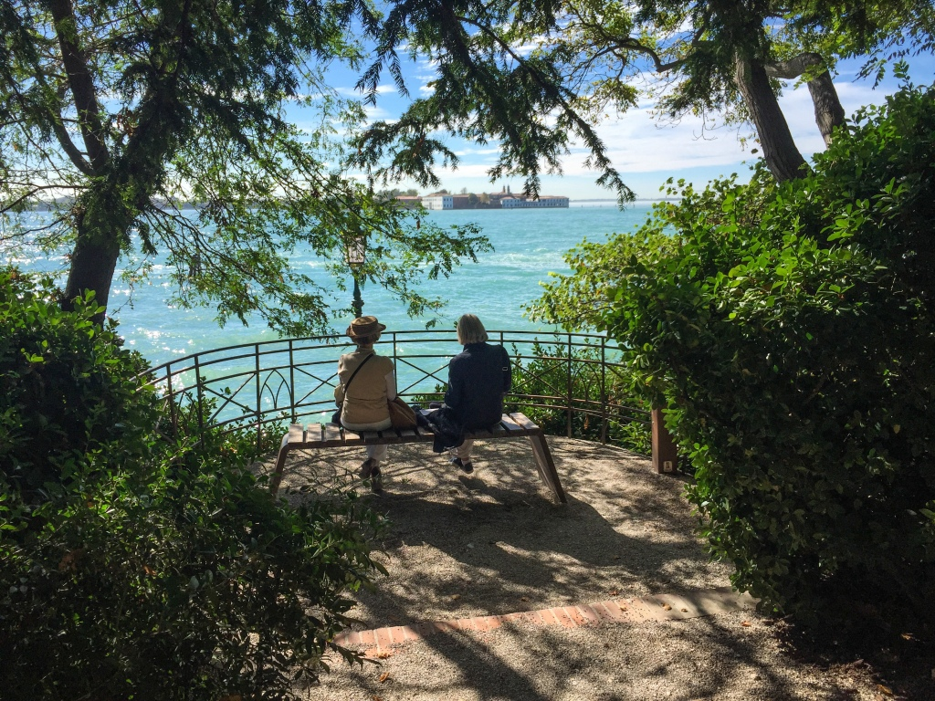 Two ladies sitting on a park bench enjoying the gorgeous view of the Mediterranean Sea in Venice, Italy.